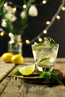A clear sparkling liquid in a glass and a lime on a wooden table with lemon, lights and a clear vase with flowers in the background.