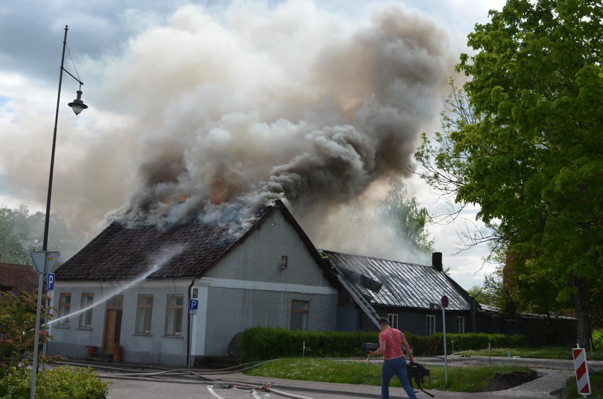 Dūmi ceļas no degošās ēkas, kamēr ugunsdzēsēji dzesē ēkas jumtu