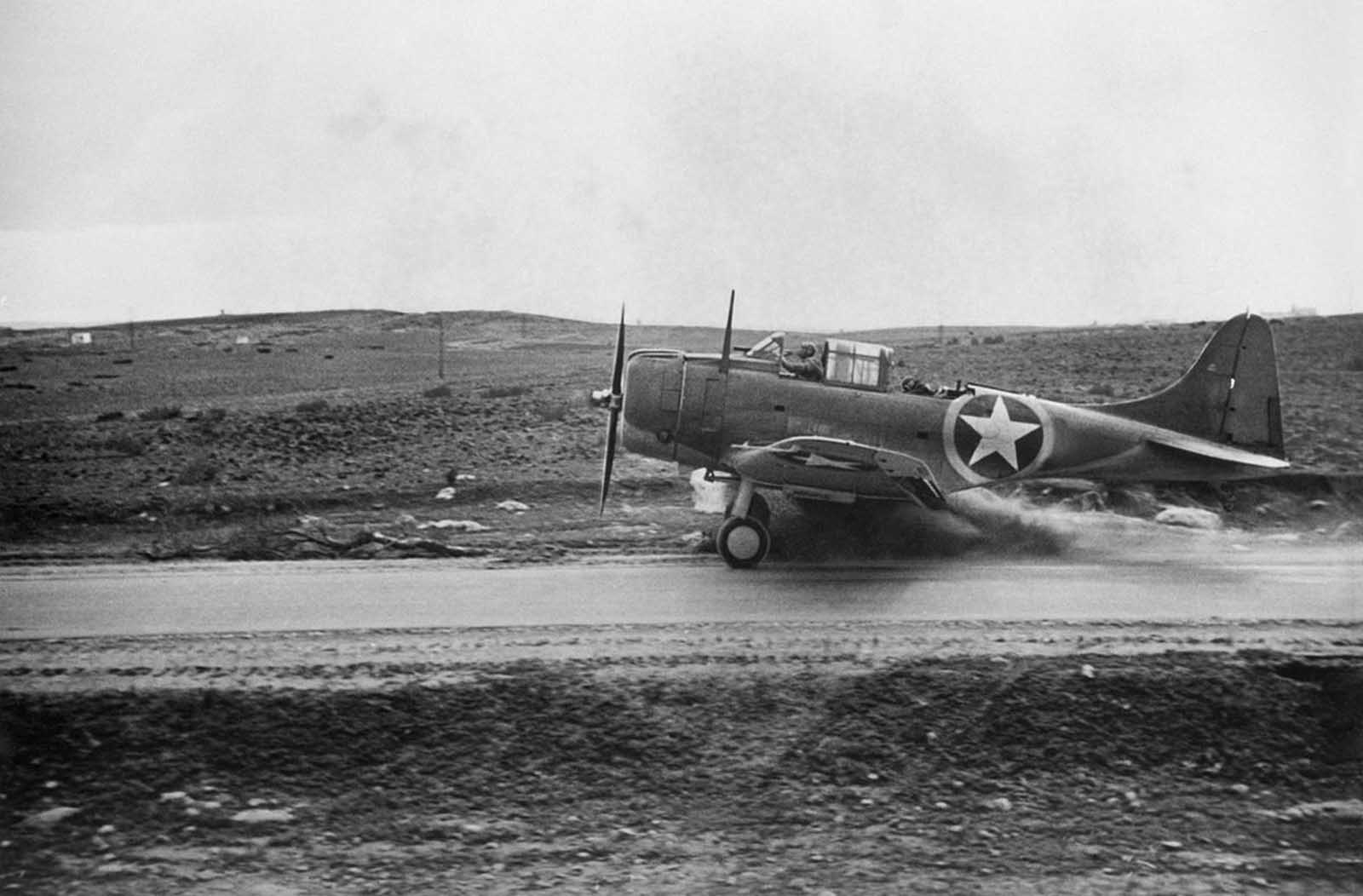A U.S. Navy dive-bomber uses a road as a runway near Safi, French Morocco, on December 11, 1942, but hits a soft shoulder in the takeoff.