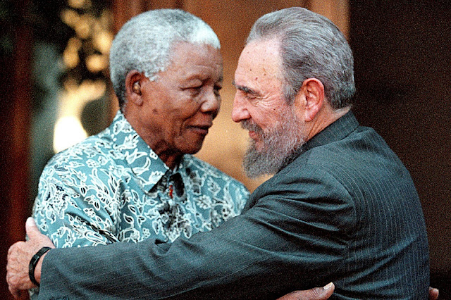 Image Attribute: Former South African President Nelson Mandela (L) hugs Cuba's President Fidel Castro during a visit to Mandela's home in Houghton, Johannesburg in this September 2, 2001 file photo.  REUTERS/Chris Kotze/File Photo