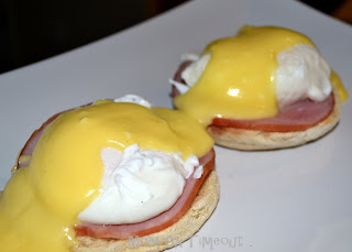 eggs benedict with hollandaise sauce on white plate