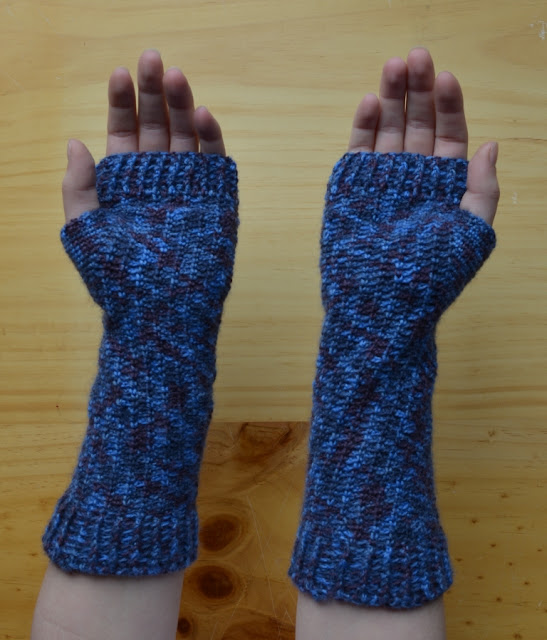 A pair of fingerless mitts with extra length at the wrist, extending two-thirds of the way up the forearm. This view is of upturned hands showing the palms of the mitts.