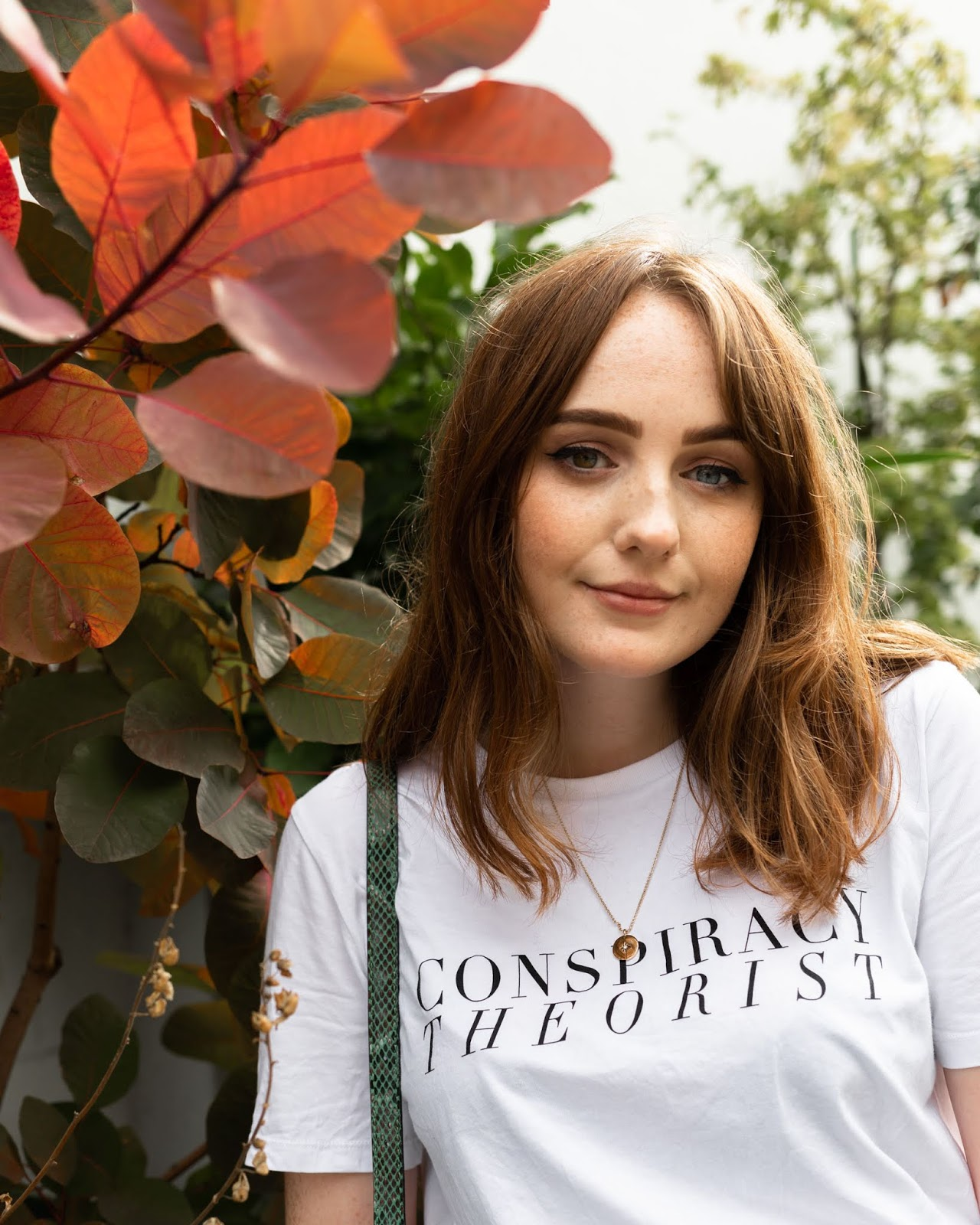 style blogger allie davies wearing white t shirt with 'conspiracy theorist' slogan t-shirt