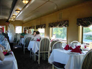 Interior of Spirit of Washington dinner train dining car with tables and people eating