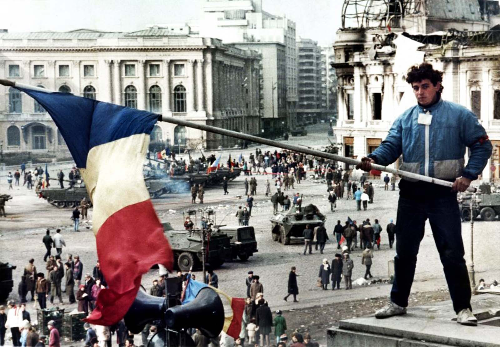 A young man waves a Romanian flag with the communist symbol cut out over Bucharest's Republic Square on 26 December 1989, the day after Ceausescu was shot.
