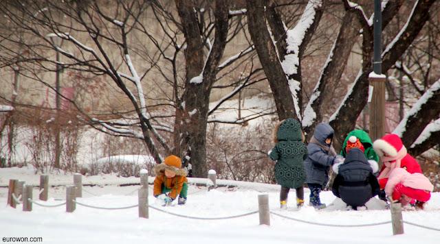 Niños coreanos jugando con la nieve
