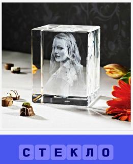 на столе стоит стекло, внутри которого сделан портрет девушки