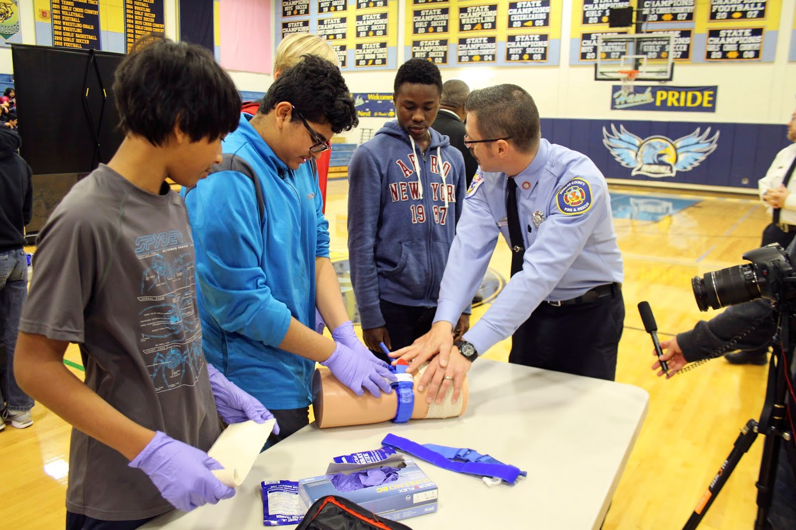 A volunteer from Howard County Fire & Rescue shows three students how to stop bleeding using a tourniquet and gauze on a model of a human limb with artificial wounds put in it. The volunteer puts pressure on the fake limb while one of the students - who is wearing gloves - manipulates the tourniquet. A camera sits on a tripod to the right, filming this, with a hand holding a microphone out to capture sound.