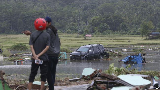 Damnificados observan un carro en medio del agua en Carita, Indonesia / AP