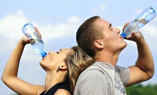 Eine Frau und ein Mann trinken jeweils aus einer Wasserflasche