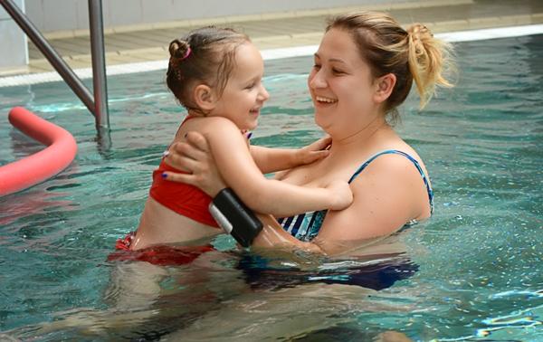 Dziewczynka z mamą na basenie, na ręce opaska kingii