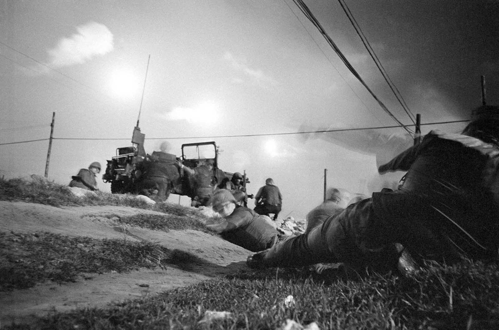 U.S. air policemen take cover and leave their jeep as they come under sniper fire near Da Nang Airbase in Vietnam on January 30, 1968, after it was hit by a rocket barrage. Flares light up the Da Nang area to make it easier to spot infiltrating guerrillas.