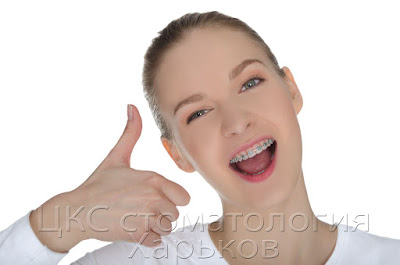 Девушка с металлическими брекетами отлично улыбается