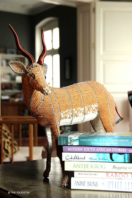 A beaded springbok next to a stash of six books from South Arrican authors.