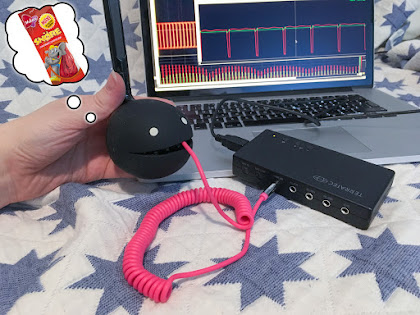 [Image: A Black Otamatone with a cable coming out of its mouth into a USB sound card. A waveform with more binary nature is displayed on a screen.]