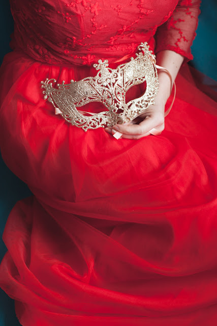 Woman wearing red dress holding a golden masquerade mask