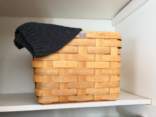 Peterboro Basket used to store winter hats and gloves in a closet shelf