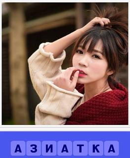 азиатка одета в кофту, рукой трогает свои губы и другой волосы