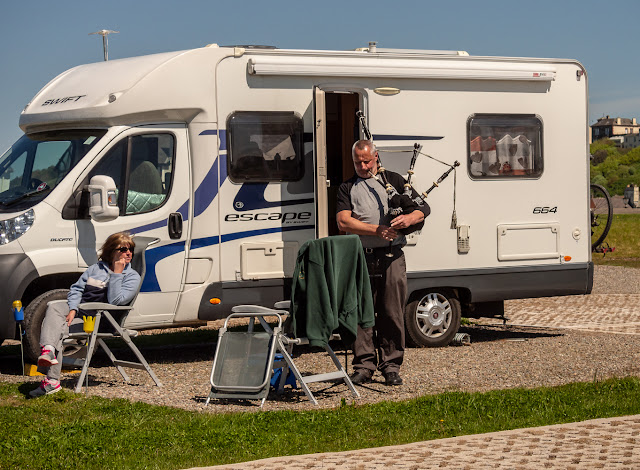 Photo of the piper practicing next to his camper van