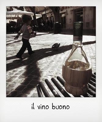Bambino che gioca e fiasco di vino Frascati