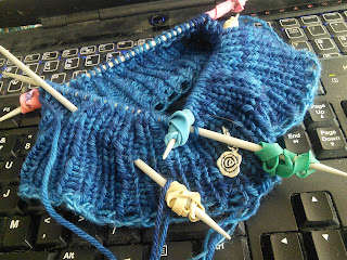 1 by 1 ribbing in-the-round on double-pointed needles.  Rubber Elastics are wrapped around the needles, and a silver rose stitch marker is clipped into the work.  Yarn is a deep blue.