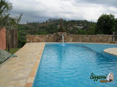 Construção do muro de pedra rústico com a construção da piscina de vinil com cascata de pedra e a bica d'água de madeira, o piso de pedra na piscina com pedra São Tomé tipo caco em sítio em Mairiporã-SP.