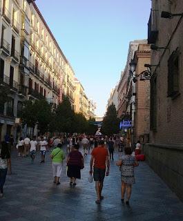 Numerosos paseantes entre edificios de viviendas y la iglesia de San Ginés, camino de la Puerta del Sol.uerta del Sol.