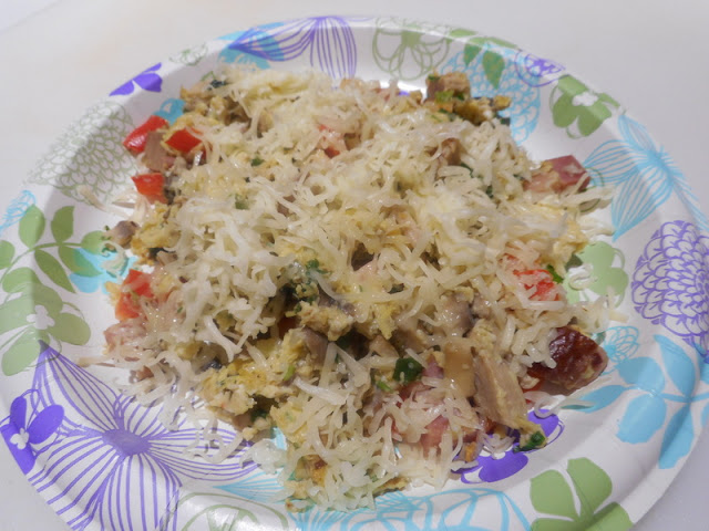 Paper Plate Filled with Scrambled Eggs, Meat, Vegetables, and Topped with Grated Cheese