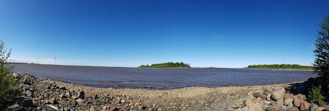 Aurinkoinen, kivikkoinen merenranta. Horisontissa saaria ja tuulivoimaloita.