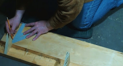 Marking off a board with a pencil and speed square
