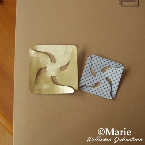 Pinwheel paper shapes in gold and green cut out ready for folding