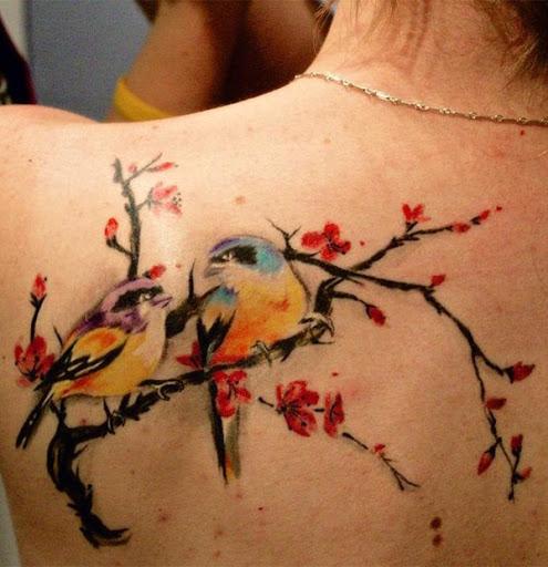 Bela flor de cerejeira tatuagem sobre os ombros com as duas aves. As aves dar as flores de cerejeira e até mesmo romântico vibe como eles olham para o outro enquanto silenciosamente passando o tempo no ramo de árvore. (Foto: Fontes de imagem)