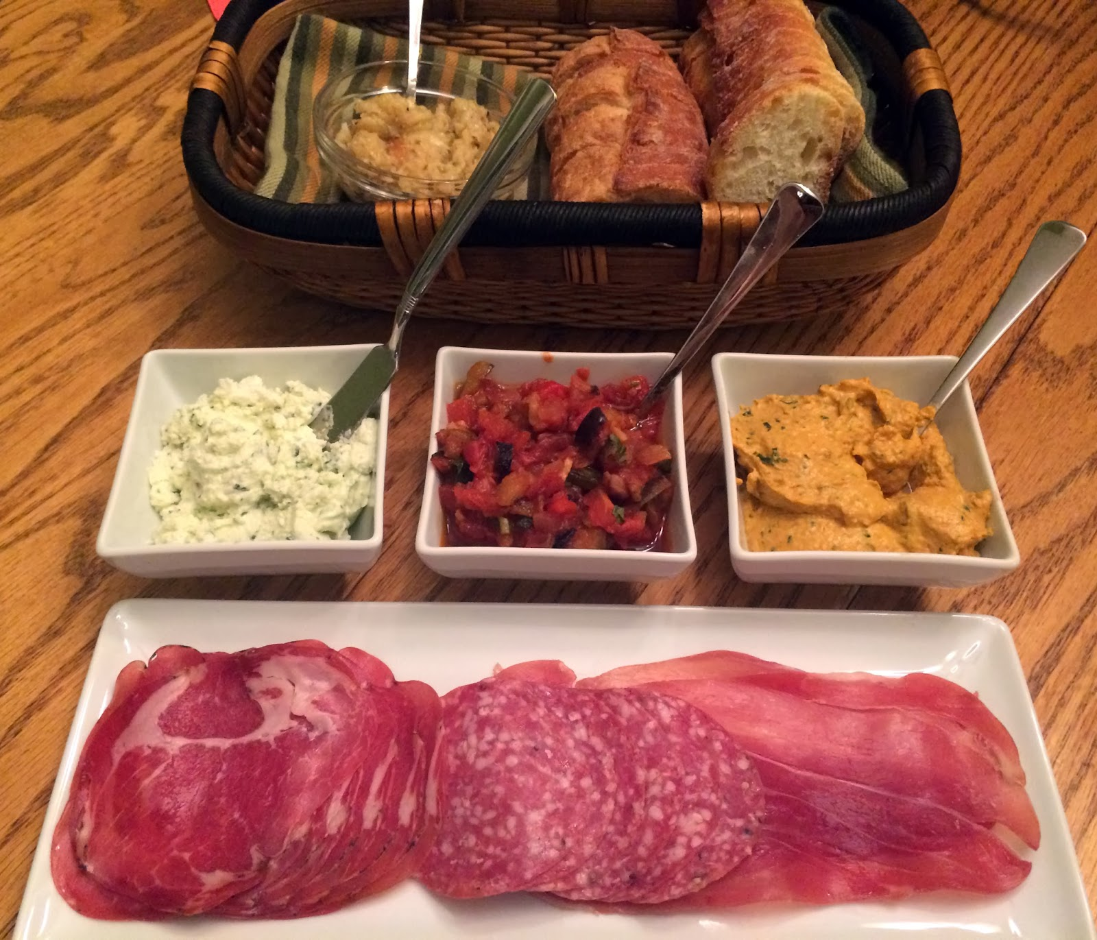 appetizer platter with various spreads and cured meats - with baguette