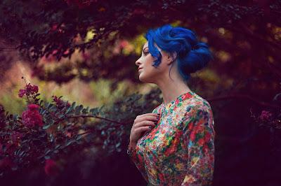 Preciosa chica con pelo azul y vestido de colores con flores de fondo