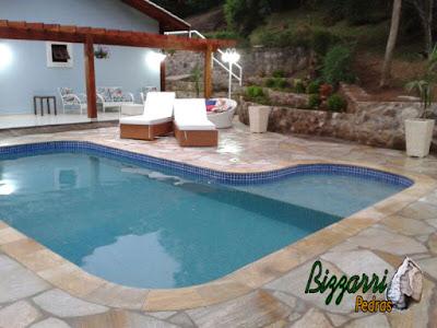 Construção de piscina de concreto com o revestimento de azulejo, o piso da piscina com pedra São Tomé tipo cacão, o muro de pedra e o pergolado de madeira.