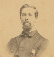 A photograph of a bearded man in uniform.