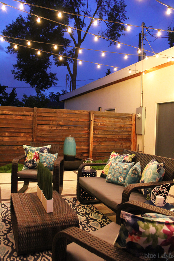 Patio with string lights between house and garage