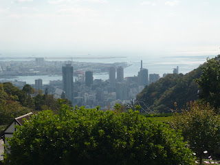 View of Kobe City nistled between two sides of the Nunobiki Herb Garden mountain with Rokko Island and Kobe Airport visible in the shining ocean
