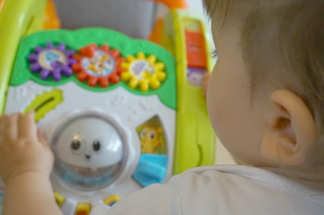 toddler playing with the little tikes light 'n' go walker