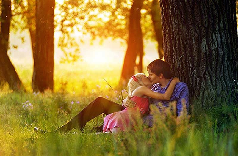 Beautiful Couple Kissing under Tree