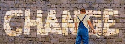Haalaripukuinen mies on maalannut tiiliseinään tekstin CHANGE.