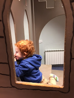 Toddler in an indoor play castle