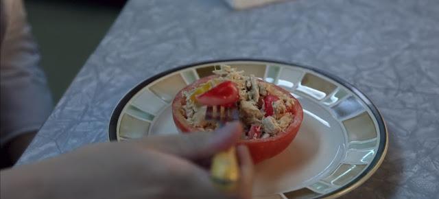 vemos la mano de Liv sosteniendo un tenedor con un trozo de tomate y la ensalada sobre un plato nacarado