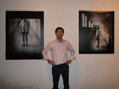 Toshi Kazama poses with pictures of a Taiwanese death row inmate.