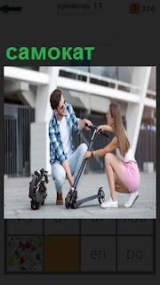 Парень помогает девушке настроить правильно самокат и учит на нем ездить