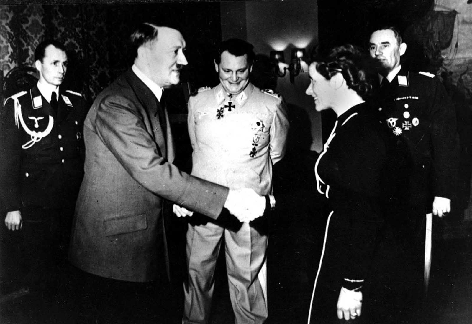 he German Aviatrix, Captain Hanna Reitsch, shakes hands with German chancellor Adolf Hitler after being awarded the Iron Cross second class at the Reich Chancellory in Berlin, Germany, in April 1941, for her service in the development of airplane armament instruments during World War II. In back, center is Reichsmarshal Hermann Goering. At the extreme right is Lt. Gen. Karl Bodenschatz of the German air ministry.
