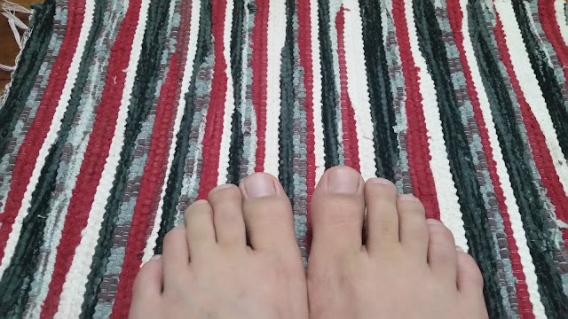 A clean feet rested in a colorful striped rug