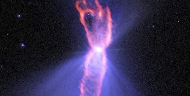 Composite image of the Boomerang Nebula, a pre-planetary nebula produced by a dying star. ALMA observations (orange) showing the hourglass-shaped outflow, which is embedded inside a roughly round ultra-cold outflow. The hourglass outflow stretches more than three trillion kilometers from end to end (about 21,000 times the distance from the Sun to the Earth), and is the result of a jet that is being fired by the central star, sweeping up the inner regions of the ultra-cold outflow like a snow-plow. The ultra-cold outflow is about 10 times bigger. The ALMA data are shown on top of an image from the Hubble Space Telescope (blue). Credit: ALMA (ESO/NAOJ/NRAO); NASA/ESA Hubble; NRAO/AUI/NSF