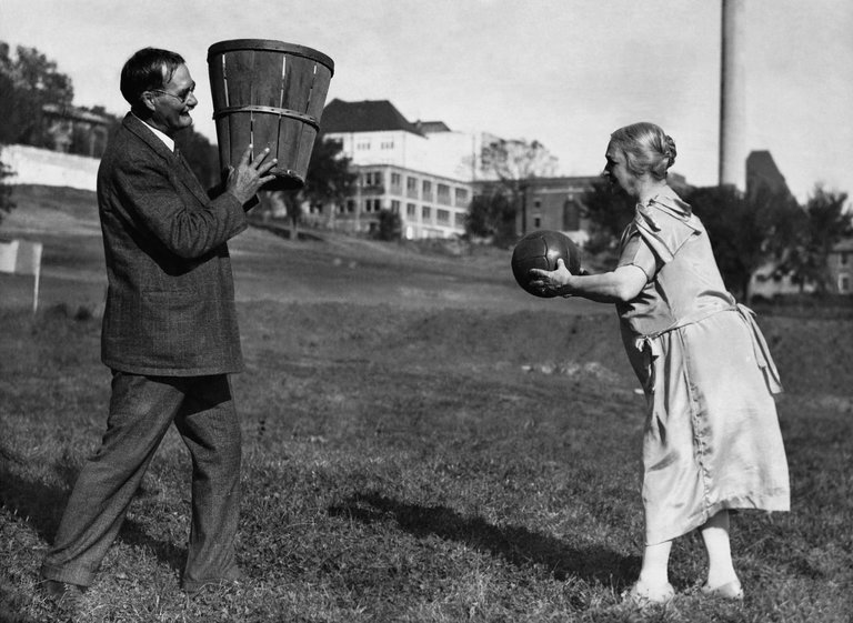 Inventor of Basketball, James Naismith, holding a fruit basket for his wife while she makes a basket. Baskets and Ladders. marchmatron.com