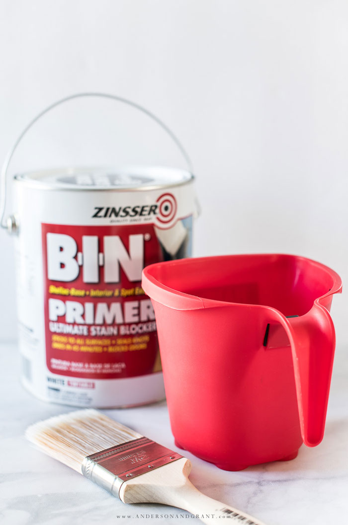 Paint cup, primer, and paint brush